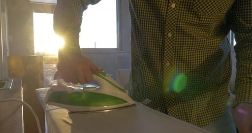 Man ironing shirt in sunny room Footage
