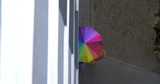 Man and woman under colorful umbrella Footage