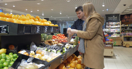 Happy Couple Choosing Oranges In Supermarket Footage
