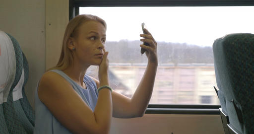 Young woman putting make-up in train Footage