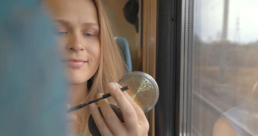 Woman going by train and putting on make-up Footage