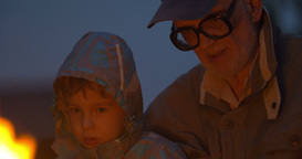 Elderly man sitting with small boy near campfire Footage
