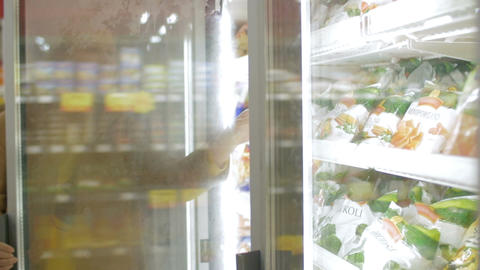Woman taking frozen product in the shop fridge Footage