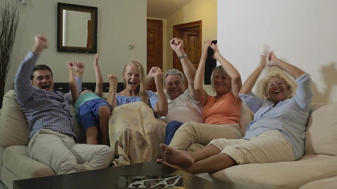 Big excited family watching sport game on TV Footage
