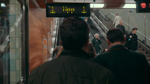 People riding up and down escalators in subway Footage