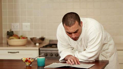 Smiling man wearing bathrobe reading newspaper Footage