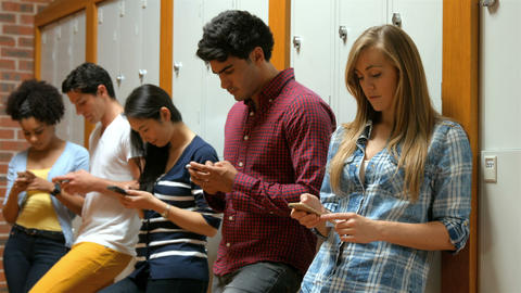 Students on their smartphone leaning on lockers Footage