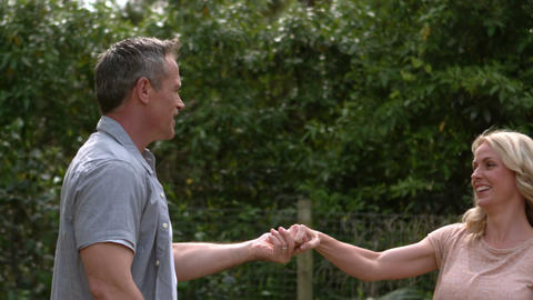 Happy adult couple dancing in the garden Stock Video Footage