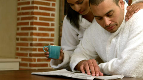 Couple reading newspaper while they having breakfast Footage
