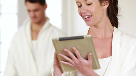 Happy couple using tablet and ironing clothes Footage