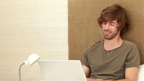 Man working on a laptop sitting on the bed Footage