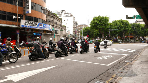 Motorbike Flock Stand On Red Light, Rush Forward And Turn Left On Green Signal stock footage