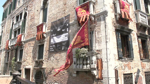 Venice flags blows on old house at canal Footage