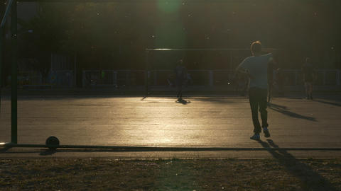4K Ungraded: Teenagers Play Football at Sunset Footage