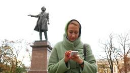 Making selfie against poet sculpture, autumn city square, portrait view Footage