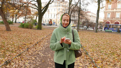 Young woman walks while using smartphone, move through autumn park Footage