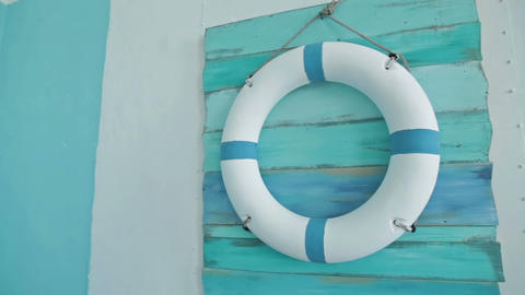 Life buoy on board on it hanging on blue wall Footage