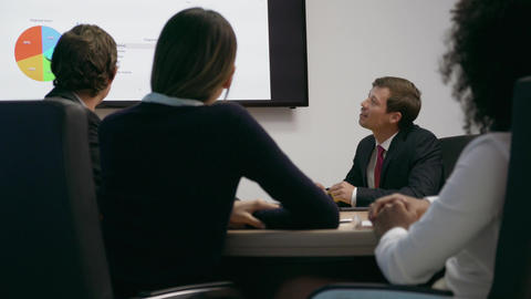 5 Business People In Office Meeting Room Looking Charts On TV Footage