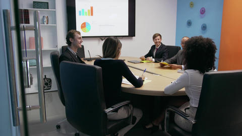 7 Business People In Office Meeting Room With Charts On TV Footage