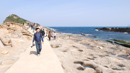 Asian people walk along pathway, sunny Yehliu Geopark cape view Footage