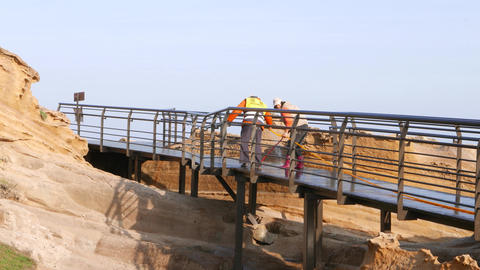 Two people wash elevated pathway in geopark pour from hose, evening light Footage