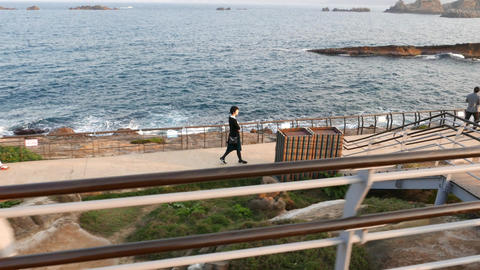 Woman walk along concrete pathway on sea shore. View from side above Footage