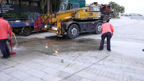 Cleaners wash paving tiles, pour water from hose and wipe by mop Footage