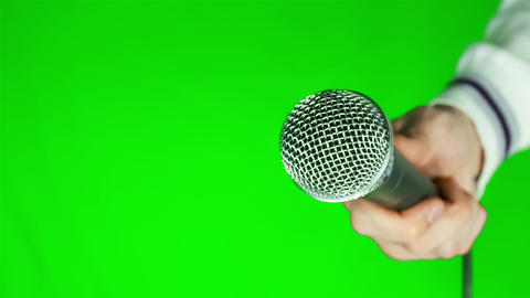 Man holding a microphone on a green background Footage