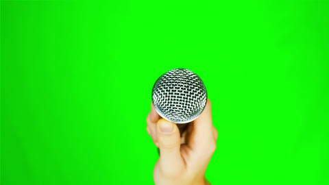 Man holding a microphone on a green background Live Action