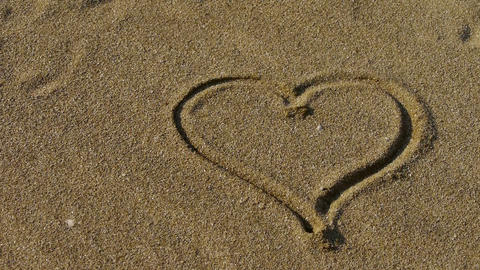 heart on golden sandy beach,wind blow sand Stock Video Footage