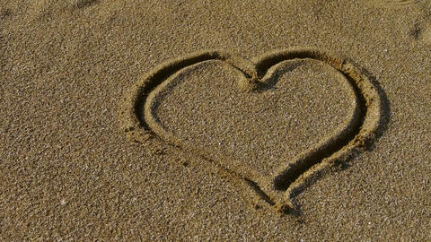 a human hand use conch drawing heart sign on golden sand Footage