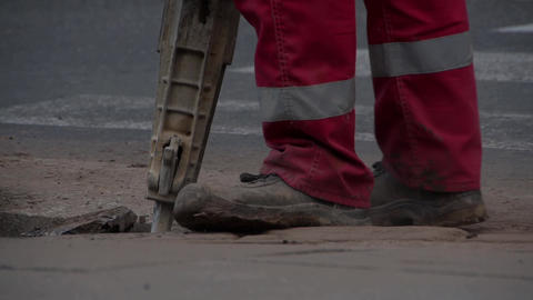 Worker crushes asphalt with pneumatic hammer Footage
