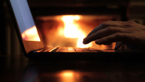 man working with a laptop in front of fireplace, close range view Footage