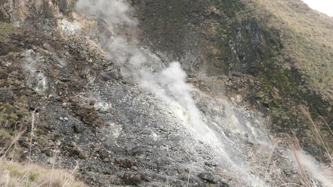 Fumarole steam, rising up from rocky exposed slope of the mountain Footage