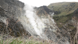 Solfatara at open side of mountain, emits toxic fumes, big white vapour flow Footage
