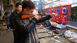Young man shooting from toy rifle, shooting gallery Live Action