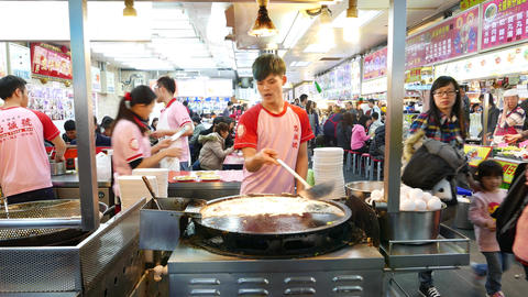 Young man cook oyster omelette at large round pan, food court kitchen, sound Footage