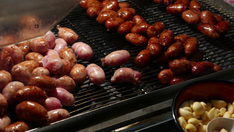 Short chinese sausages on grill grate, cook in progress, close up Footage