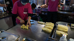 Woman roll and flatten dough ball, to make pancake shape. Repeating process Footage