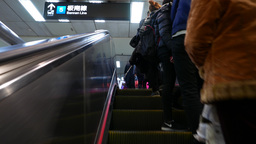 Walking up escalator at metro station, passengers standing on right Footage