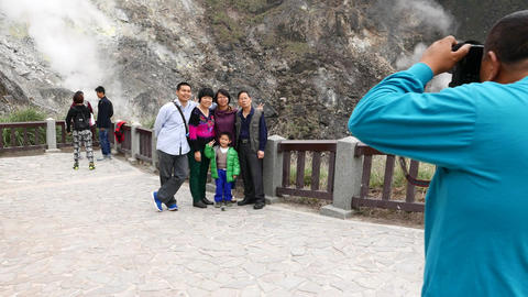 Asian family take group picture against fumarole steam from mountain slope Footage