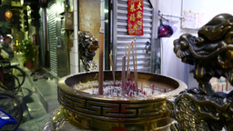 Incense sticks in urn with dragons in front of religion shop Footage