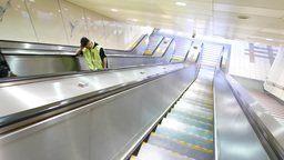 Travelling down on the escalator, bright glossy tunnel, people on the way Footage