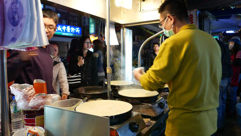 Chinese pancake cooking on night street, from behind the kitchener Footage