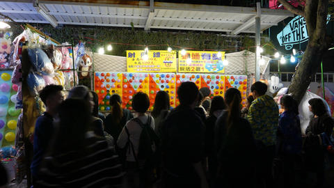 Balloon shooting range at night market, seen through crowd silhouettes Footage