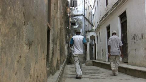 People Walking On Narrow Street Amidst Houses Footage