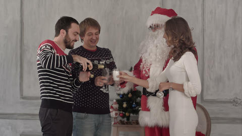 Young happy smiling friends with santa open and drink champagne. Christmas and H Footage