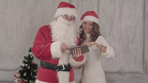 Loughing Santa and beautiful woman use tablet Footage