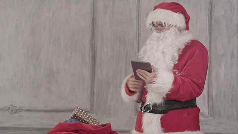 Santa claus with tablet pc computer checking gift bag Footage