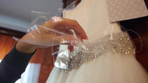 Woman unwrap the plastic protection on a wedding dress waist 61a Footage